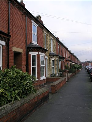 Two-storey terraced houses on Scorer Street with bay windows on the ground floor of the properties; a low wall separates the properties from the path in front.