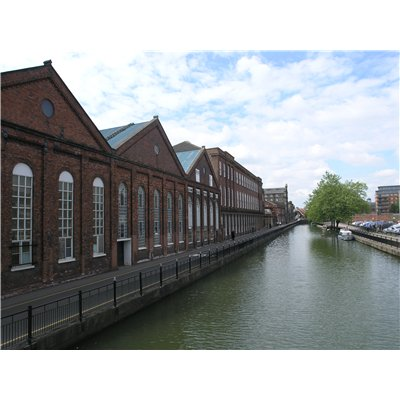 Buildings on Waterside South, which have a strong building line as they are positioned at the back of the footway, facing onto the river. The building are red bricked and have pained glass windows.