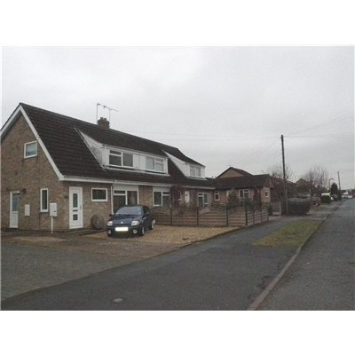 One and a half storey houses setback form the road with driveways and gardens.