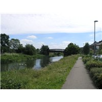 An area of green space in the form of a corridor along the River Witham and South Delph Drain. It has natural, planted edges for the most part and brings a rural aspect all the way into the city centre. In the background is a bridge over the River Witham.